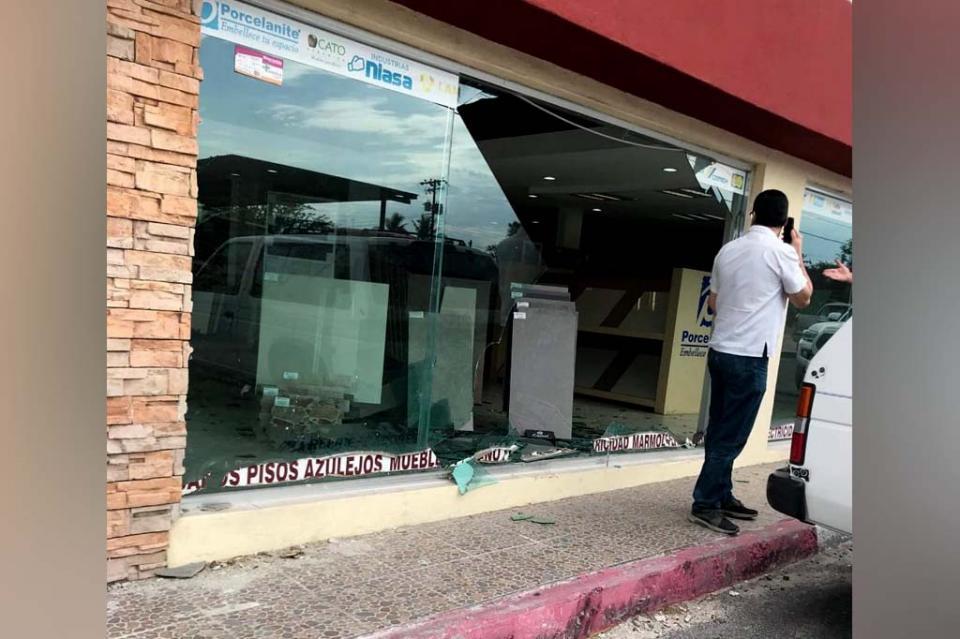 En La Paz, conductor reversea y se va contra vidrio de un negocio