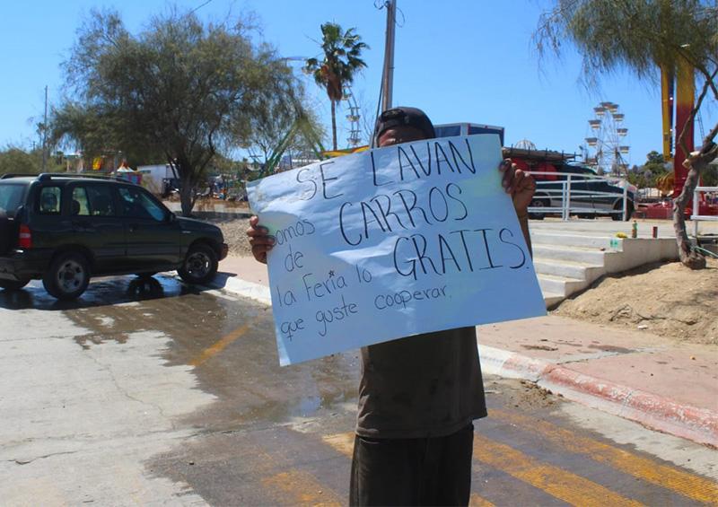Comerciantes de la feria se encuentran lavando carros para juntar dinero