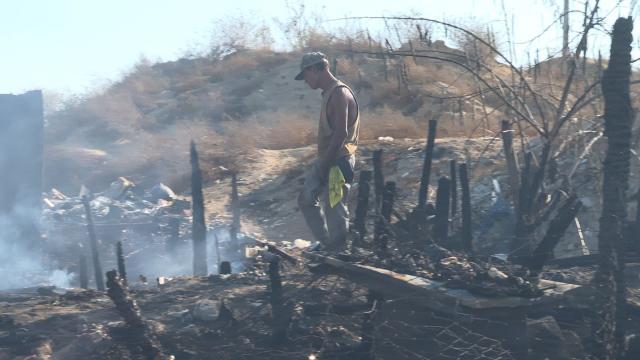 Hombre caminando sobre una vivienda incendiada