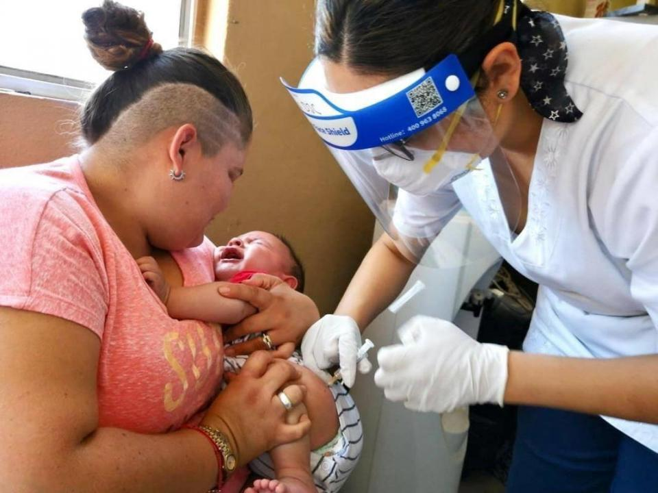Enfermera vacuna a un bebé