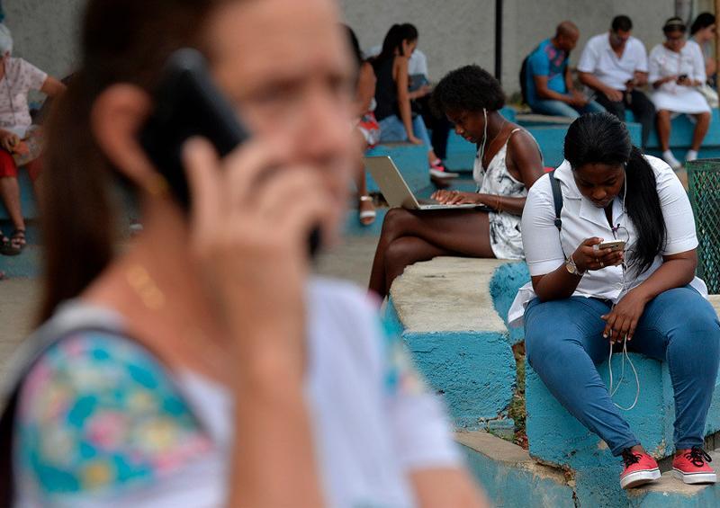 Personas usando teléfonos y computadoras en una plaza pública de La Habana